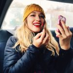 a young woman putting make-up on in a car